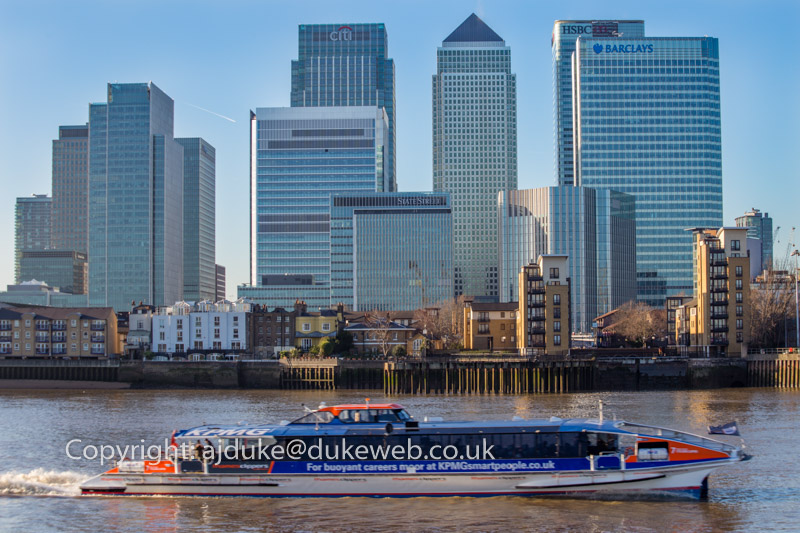 Canary Wharf and other skyscrapers on the Isle of Dogs, river Thames and boat taxi, London