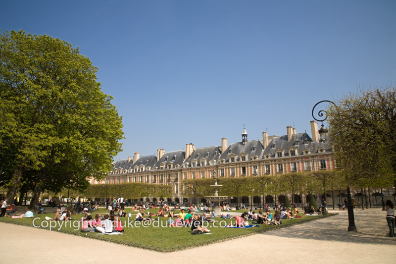 People relaxing in the gardens of the Place des Vosges Paris