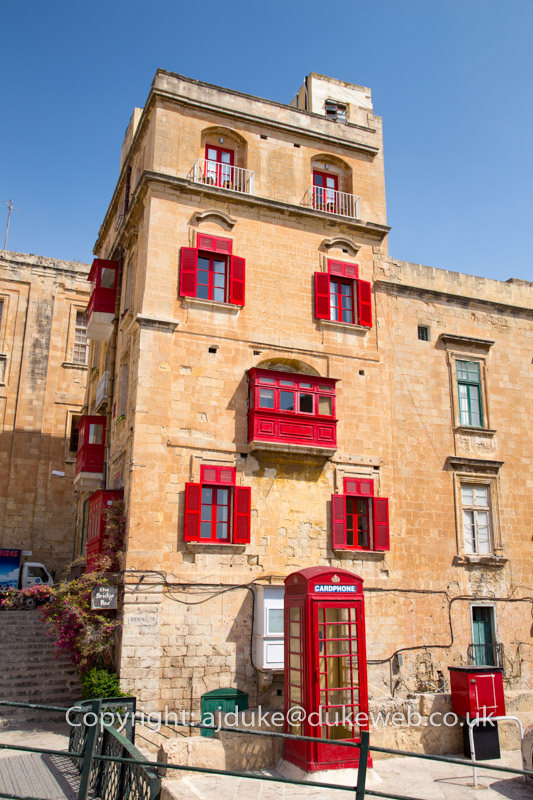 Valetta buildings scene showing characteristic Maltese balconies and British red phonebox, Malta